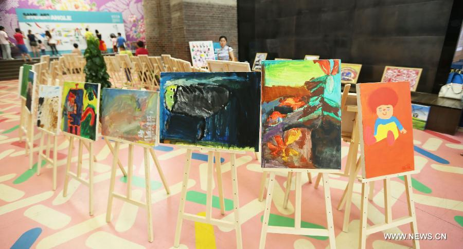 Visitors view paintings at a painting exhibition at the 798 art area in Beijing, capital of China, May 25, 2013. A two-day exhibition kicked off on Saturday, displaying paintings created by over 20 mentally retarded children from Chaoyang Anhua School. (Xinhua)
