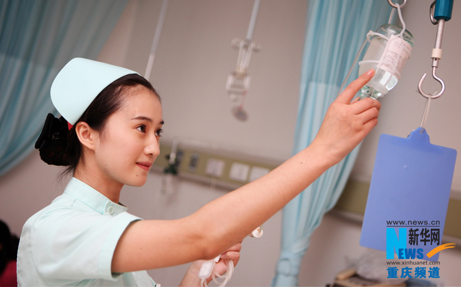 Tan Ling, a nurse in Chongqing South West Hospital, checks a patient's infusion bottle. (Xinhua/Peng Bo)
