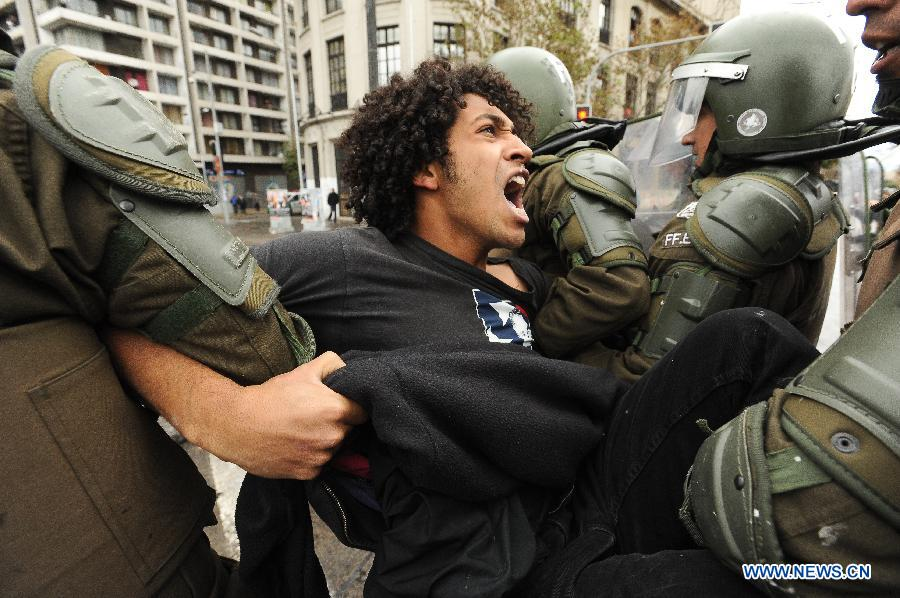 Riot policemen arrest a man during a protest called by the Chilean Coordinating Assembly of High School Students (ACES), the Chilean National Coordination of Students of High School (Cones), the Council of Student Federations of Chile (CONFECH) and the Movement of Students of Private Higher Education (MESUP), in Santiago, capital of Chile, on May 28, 2013. The students demanded a dignified and free education without lucre, according to local media. (Xinhua/Jorge Villegas)