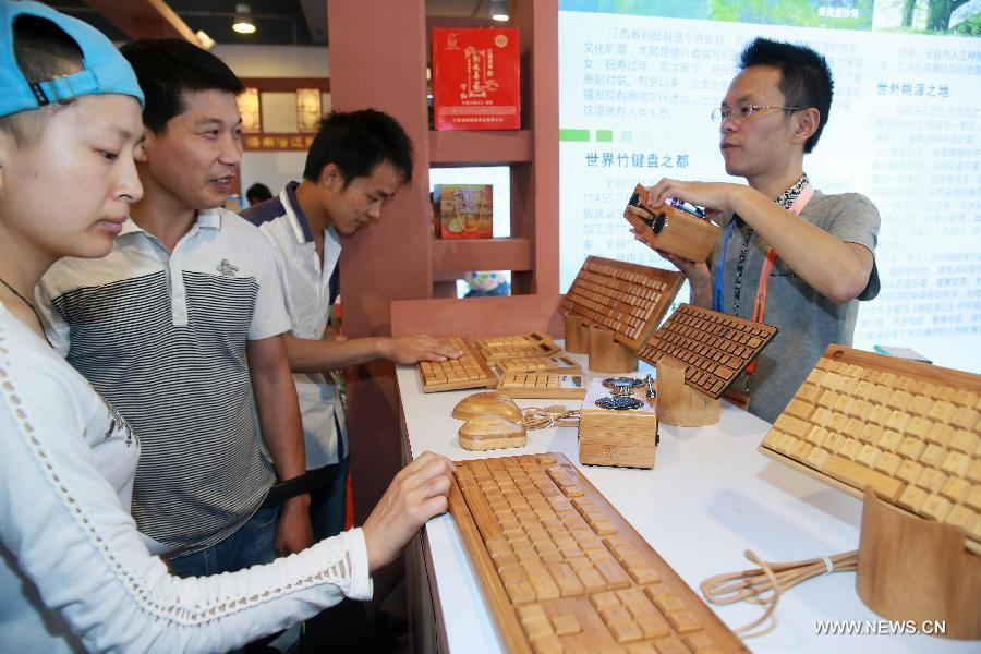 A staff member introduces bamboo-made electronic products at China Beijing International Fair for Trade in Services (Beijing Fair) in Beijing, capital of China, May 31, 2013. (Xinhua/Chen Jingsu)