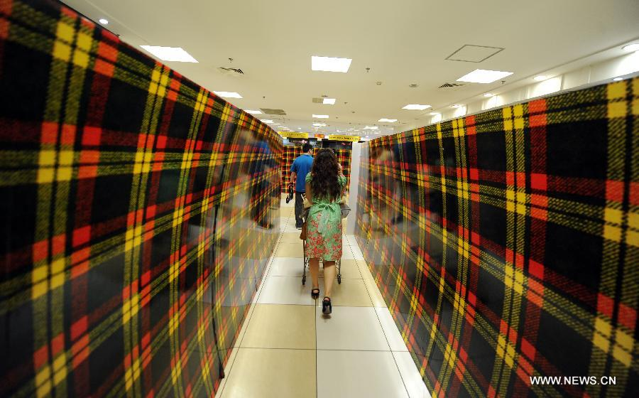 Customers walk between the covered shelves at the Japan-based Isetan Supermarket in Shenyang, capital of northeast China's Liaoning Province, May 31, 2013. Isetan Mitsukoshi Holdings Ltd. closed its department store in Shenyang on June 1, 2013 amid poor business conditions. Earlier, Isetan Mitsukoshi closed other two stores respectively in east China's Shanghai and Jinan. (Xinhua/Yao Jianfeng)