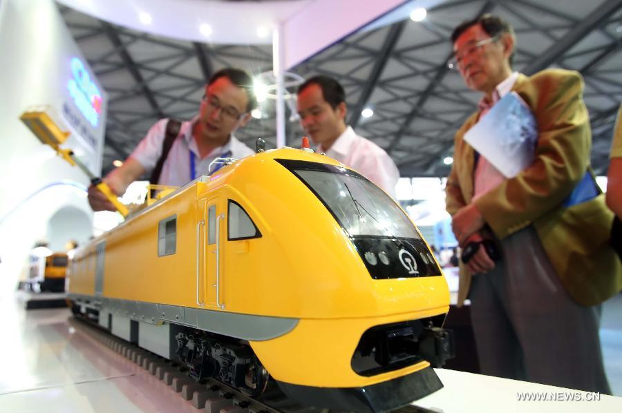 Visitors surround a locomotive model at the 8th Rail and Metro China exhibition held in Shanghai, east China, June 4, 2013. The exhibition, opened here on Tuesday, has attracted over 180 exhibitors from 12 countries and regions. (Xinhua/Liu Changlong)