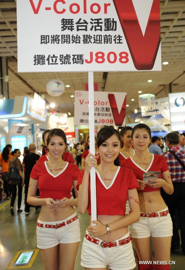 Employees raise advertisements for their pavilion at Computex Taipei 2013 exhibition, in Taipei, southeast China's Taiwan, June 4, 2013. The five-day exhibition opened here on Tuesday. (Xinhua/Tao Ming)