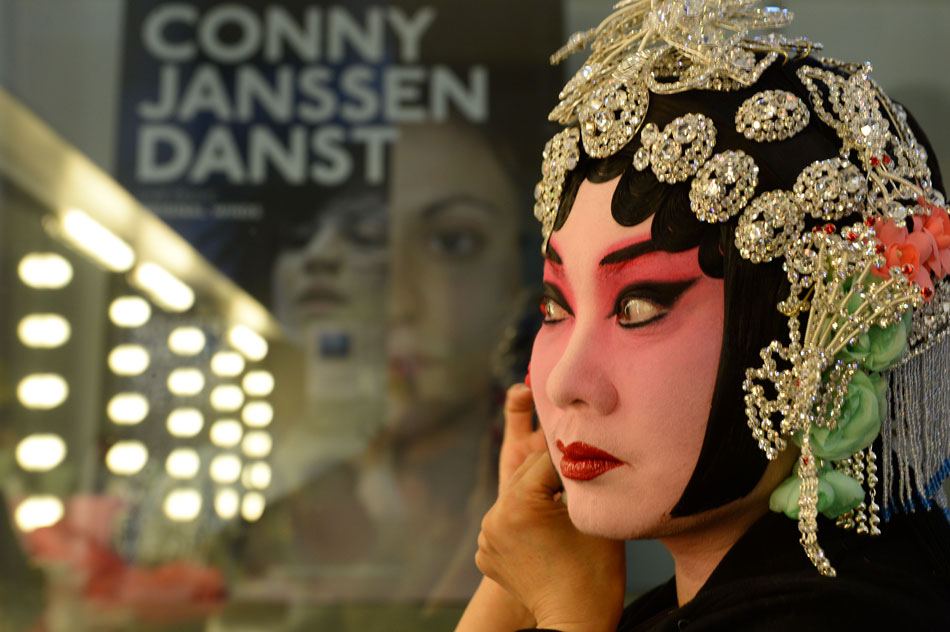 Wang Rongrong, well known Peking Opera actoress, puts on makeup before performance in Nederlands Dans Theater in Hague, the Netherlands on May 23, 2013.  (Photo/Xinhua)