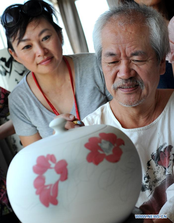 A visitor learns painting technique from Taiwan artist Chen Shi Hou (R) in the town of Yingge of Xinbei City in southeast China's Taiwan, June 8, 2013. Over 100 artists have set up workshops in Yingge, which is famous for ceramics production, providing opportunities for visitors to experience the process of making porcelains. (Xinhua/Tao Ming)