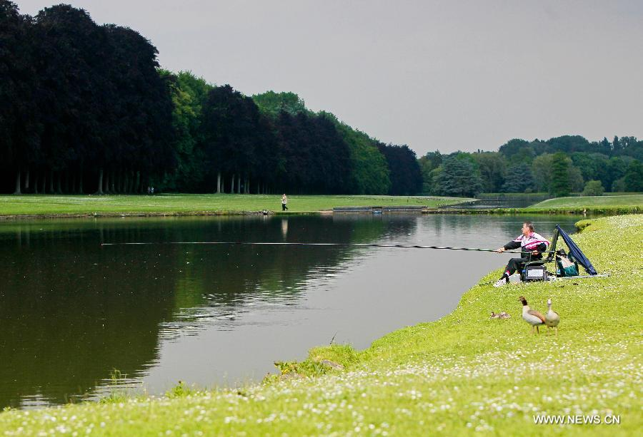 A man fishes at a park in the eastern suburbs of Brussels, capital of Belgium, on June 11, 2013. Local residents go to parks to enjoy the sunshine after experiencing a long and gloomy spring this year. (Xinhua/Zhou Lei)