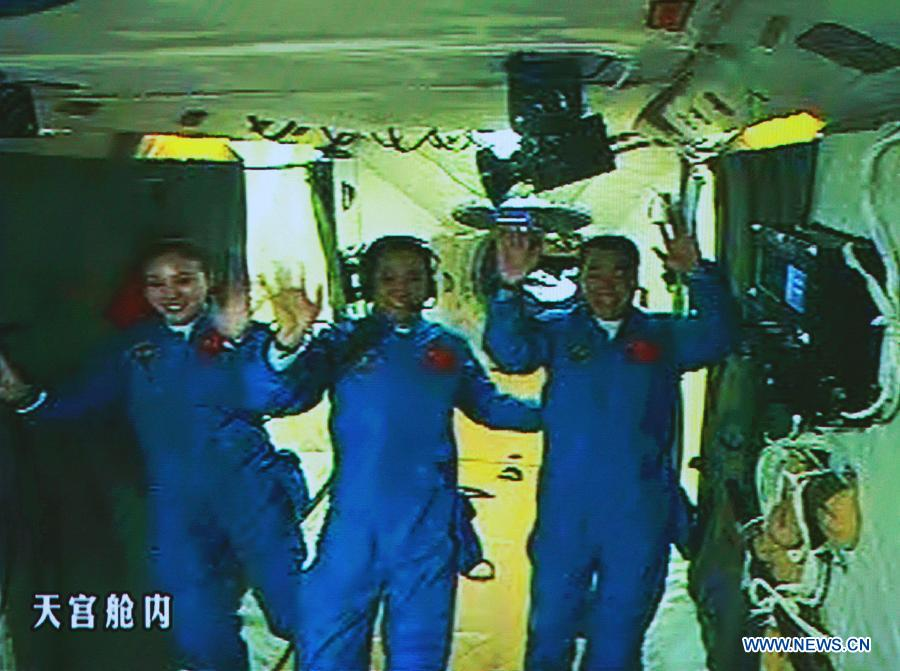 Photo taken on June 13, 2013 shows the screen at the Beijing Aerospace Control Center showing the three Chinese astronauts waving hands at the Tiangong-1 space module. China's Shenzhou-10 manned spacecraft successfully completed an automated docking with the orbiting Tiangong-1 space module at 1:18 p.m. Thursday and the astronauts Nie Haisheng, Zhang Xiaoguang and Wang Yaping opened the hatch of Tiangong-1 at 4:17 p.m. (Xinhua/Wang Yongzhuo)