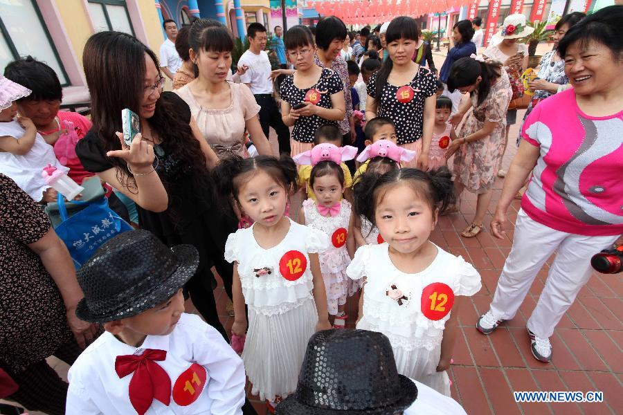 Twins attend the 2013 Shandong (Weifang) First Twin Cultural Festival in Weifang, east China's Shandong Province, June 15, 2013. The festival, in which more than 60 pairs of twins and multiple births from Weifang City showed their talents and exchanged with each others, opened here on Saturday.(Xinhua/Zhang Chi)