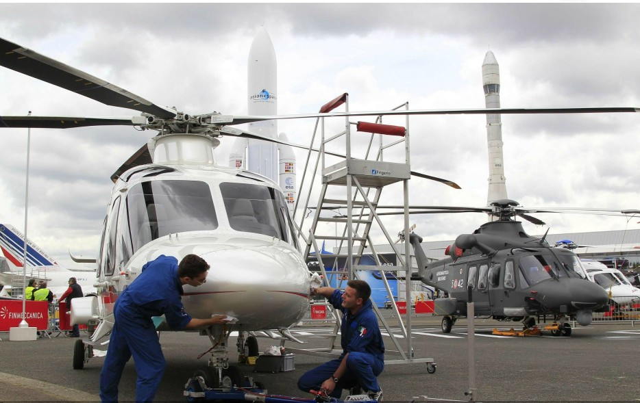 Workers clean an AgustaWestland helicopter AW169 in static display, two days before the opening of the 50th Paris Air Show, at the Le Bourget airport near Paris, June 15, 2013. (Photo Source: chinadaily.com.cn)