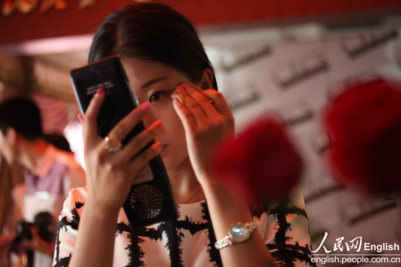 "A candidate applies cosmetics during a ""rich blind date"" held in Jinan, capital city of east China's Shandong province, June 16, 2013. Fifty candidates taking part in the ""rich blind date"" will be selected to attend a party for rich individuals to be held overseas in July. (Photo by Pan Yongqiang/ CFP)"