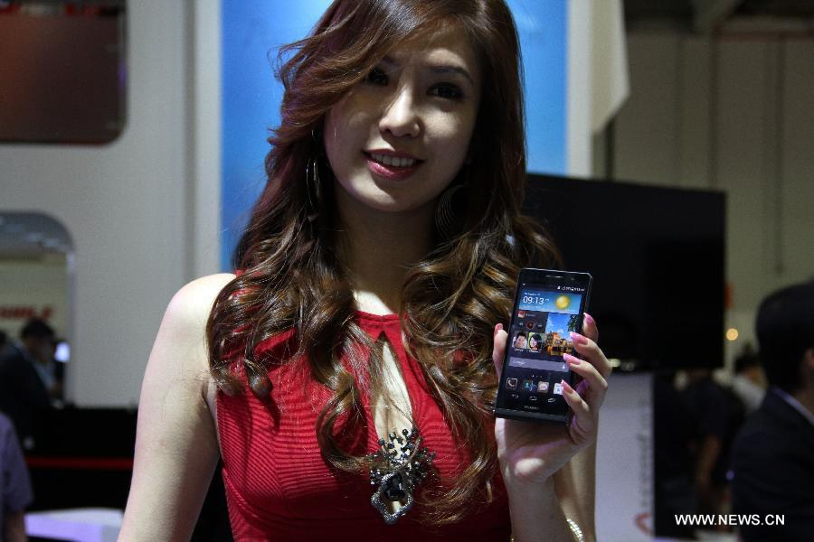 A model shows Huawei Ascend P6 smartphone at Huawei's booth during the CommunicAsia in Singapore, on June 19, 2013. International telecommunications giant Huawei unveiled its latest flagship device Ascend P6 in Singapore on Wednesday, marketing it as the thinnest smartphone in the world. (Xinhua/Chen Jipeng)