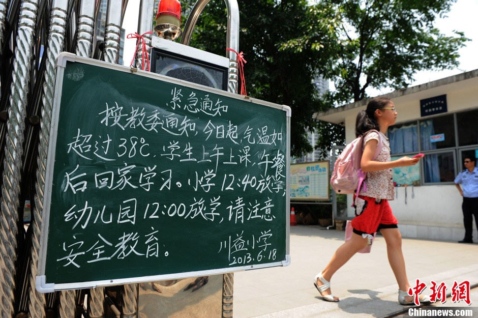 A notice at the gate of a school in Chongqing tells the students to study at home in the afternoon because of the hot weather on June 16, 2013. The temperature in Chongqing reached 38 degrees Celsius on the day. (Photo/Chinanews)