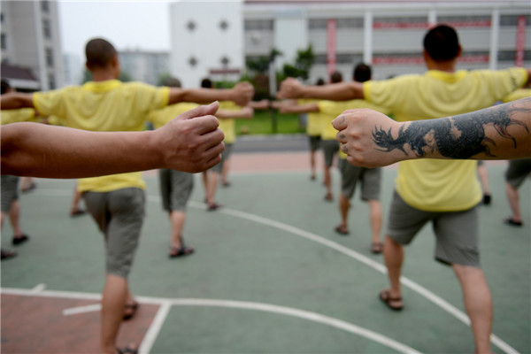 "Addicts do group exercises at a drug rehabilitation center in Anhui province, June 19, 2013. ""The days when I took drugs, I changed a lot in temper and became crusty and paranoid. After a year of drug control in the center, I've shrugged off many bad habits and become much better in body and mentality. Now I'm eager to find a job in my hometown after my drug control ends and spend more time with my family,"" said one drug addict. There are 500 addicts at the drug rehab center, which provides them with medical treatment, psychological counseling as well as skill training to help them return to society. [Photo/Xinhua]"
