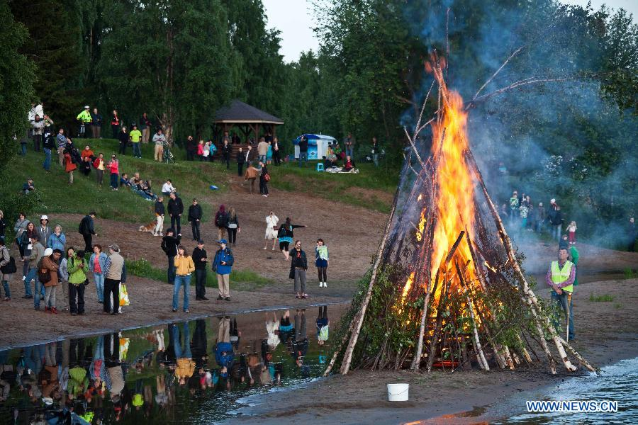 People gather around a bonfire to celebrate summer solstice in Lapland, north Finland in the Arctic Circle, in June 21, 2013. As Lapland situates in the Arctic Circle, there happens polar day in Summer solstice. Night and day the midnight sun stays above the horizon.(Xinhua/Yan Ting)