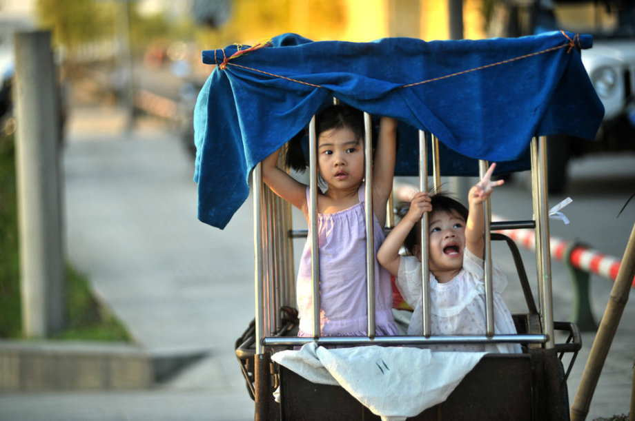 Two girls who look like 6 and 3 years old respectively are locked in a cage-like tricycle on roadside, while their grandmother is doing laundry by the river in S China's Guangxi June 18, 2013.(Photo/ youth.cn)
