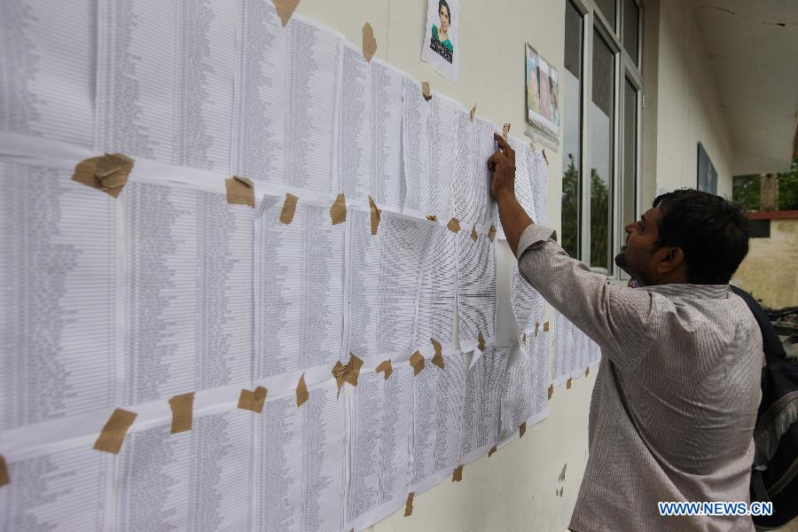 A man views information about the missing people at the helicopter airport in Dehradun, northern Indian state of Uttarakhand, June 26, 2013. There are still an estimated 7000 people stranded in the flood while authorities use military planes and helicopters in the rescue in flood-ravaged northern India. (Xinhua/Zheng Huansong)
