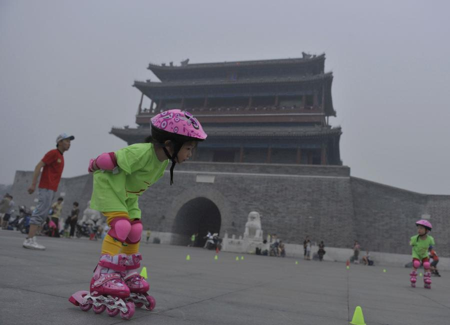 A little girl learns roller skating in haze in Beijing, capital of China, June 28, 2013. Most parts of Beijing are shrouded by severe haze on Friday. (Xinhua/Song Weiwei)