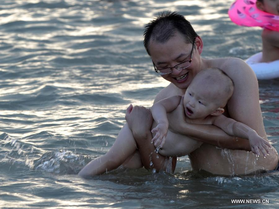 A man plays with his child in the sea near Haikou, capital of south China's Hainan Province, June 29, 2013. The highest temperature in Haikou reached 35 degree centigrade, driving local residents to the seashore. (Xinhua/Zhao Yingquan)