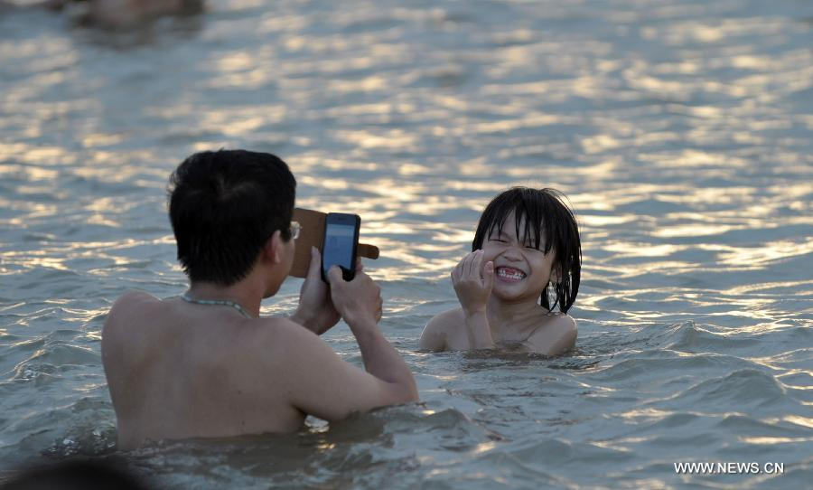 A man take photos of a child in the sea near Haikou, capital of south China's Hainan Province, June 29, 2013. The highest temperature in Haikou reached 35 degree centigrade, driving local residents to the seashore. (Xinhua/Zhao Yingquan)
