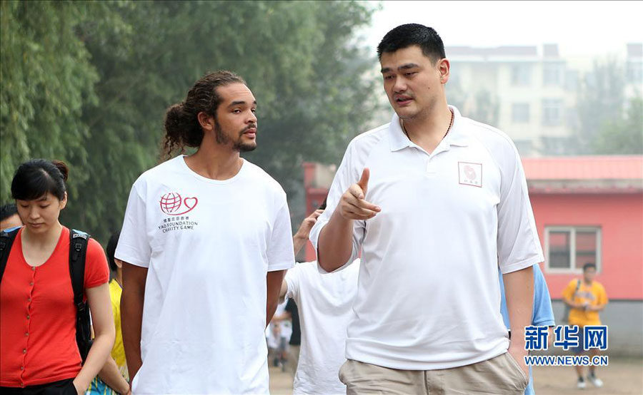 Former NBA star Yao Ming (R) talks with Joakim Noah of Chicago Bulls during their visit to a primary school for children from migrant workers' families in Changping district in the northern suburbs of Beijing, Sunday, June 30, 2013. The visit is part of the Yao Foundation charity events in 2013, which inlcude a charity basketball game on July 1, 2013 in MasterCard Center in Beijing.