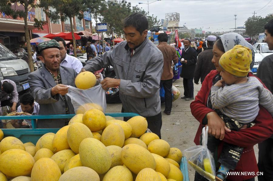 Locals buy melons at the Id Kah Bazaar in the city of Hotan, northwest China's Xinjiang Uygur Autonomous Region, July 1, 2013. (Xinhua/Zhao Ge)