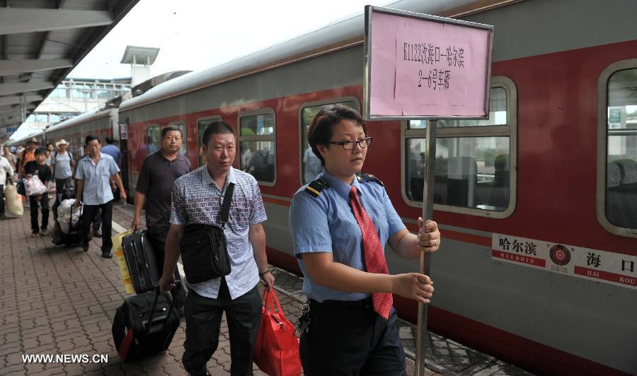 A staff member guides the passengers to aboard the first direct train from Haikou to Harbin at the Haikou Railway Station in Haikou, capital of south China's Hainan Province, July 2, 2013. The train K1122/3 from south China's Haikou to northeast China's Heilongjiang left Haikou Tuesday, a day later than its original departure date due to the tropical storm Rumbia. The train which travels 4,458 kilometers for 65 hours has connected China's southernmost capital city Haikou of Hainan Province with China's northernmost capital city Harbin of Heilongjiang Province. (Xinhua/Zhao Yingquan)