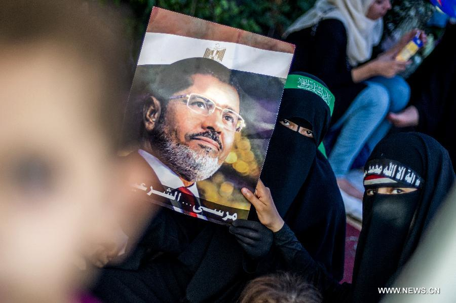 A supporter of ousted Egyptian president Mohamed Morsi holds a poster of Morsi as she rests in a tent outside Raba al-Adwyia Mosque, in Nasr City, Cairo, capital of Egypt, July 8, 2013. (Xinhua/Li Muzi)