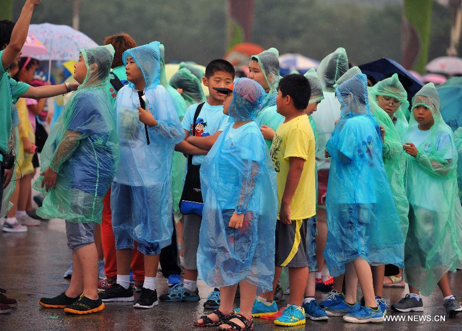 Children wearing raincoats visit the Tiananmen Square in Beijing, capital of China, July 9, 2013. Many tourists continue to come to enjoy the scenery of the capital city while Beijing witnessed frequent rainfall recently. The local meteorological observatory observatory issued a warning on torrential rains from Tuesday to Wednesday in Beijing. (Xinhua/Chen Yehua)