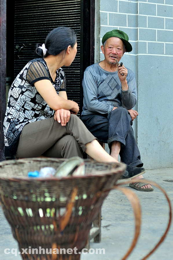 Two people chat in front of their newly built houses in the eco-migration community. The eco-migration project aims to help the poor overcome extreme difficulties in Lantian town, Chengkou county, southwest China's Chongqing. (Xinhua Photo/ Li Xiangbo)