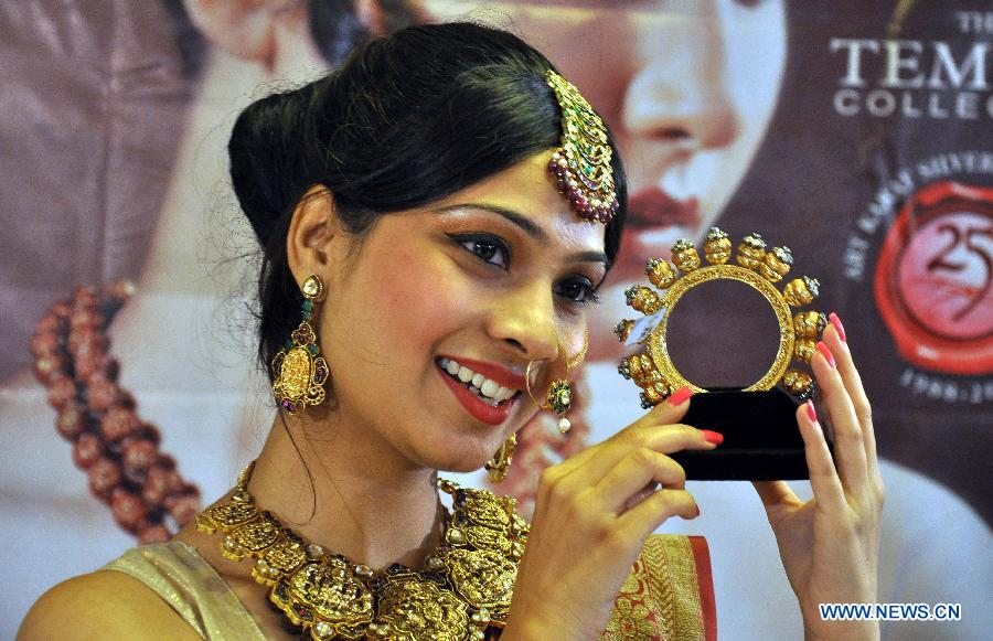 "A model displays jewelry of ancient temples of India during the exhibition ""Temple Collection"" in Bhopal, India, July 11, 2013. (Xinhua/Stringer)"