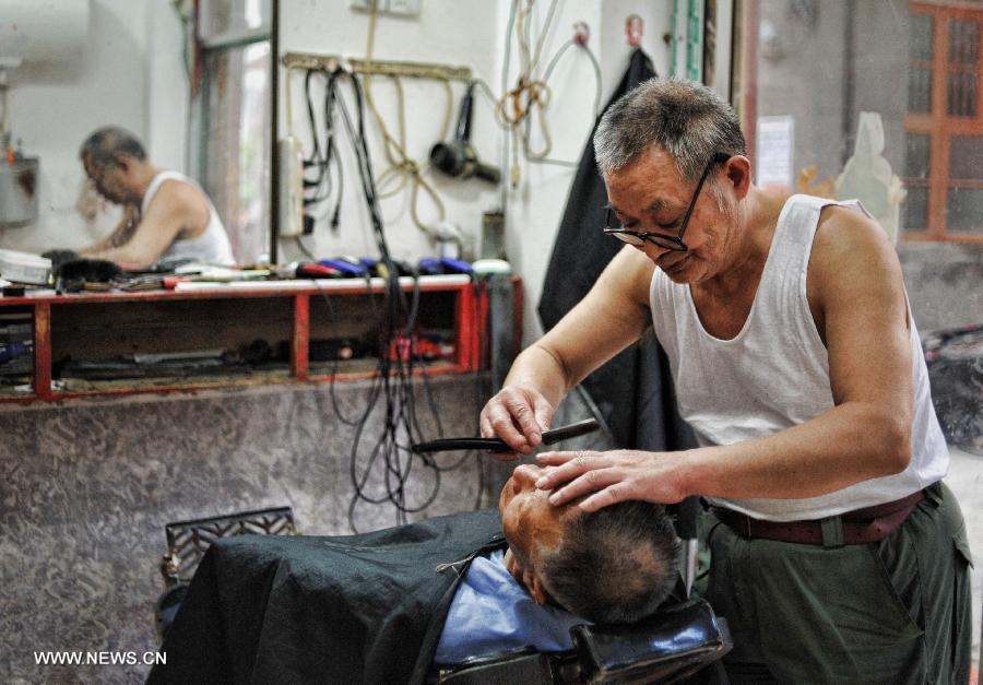 An old barber does a haircut for his customer in the Miao Autonomous County of Chengbu, central China's Hunan Province, July 13, 2013. An ecology tourism festival is held here from July 12 to 14. (Xinhua/Cheng Tingting)