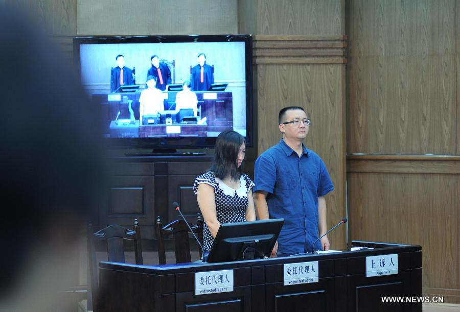 Tang Hui (L), mother of a young rape victim who sued a local authority for putting her into a labor camp, attends the court hearing in The Hunan Provincial People's High Court in Changsha, capital of central China's Hunan Province, July 15, 2013. The Hunan Provincial People's High Court on Monday ordered the Yongzhou municipal re-education through labor commission to pay Tang Hui 2,941 yuan (478 U.S. dollars) in compensation for infringing upon her personal freedom and causing mental damages. The 40-year-old mother appealed to the high court in April after the Yongzhou Intermediate People's Court denied her request for an apology and compensation from the re-education through labor commission. Tang was put into the labor camp after she publicly petitioned for harsher punishments for those found guilty of raping her daughter and forcing her into prostitution. (Xinhua/Long Hongtao)