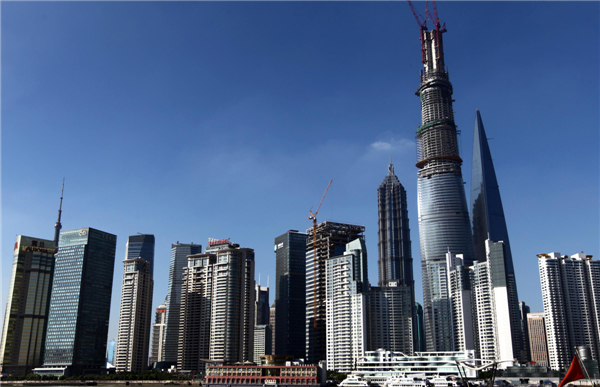 Shanghai Tower, China's tallest building when it's finished, dwarfs nearby skyscrapers in the Lujiazui finance and trade district in Shanghai's Pudong area, July 17, 2013. The structure will be capped soon with a spire, which will bring the dragon-shaped building to a height of 632 meters, dwarfing the 492-meter Shanghai World Financial Center and 421-meter Jinmao Tower. The building will be finished and open by 2015. (Photo/Xinhua)