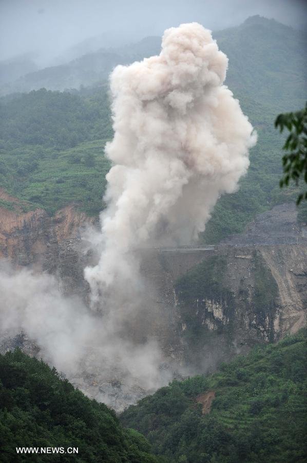 Photo taken on July 18, 2013 shows the blasting site above a barrier lake in Sanjiao Township of Hanyuan County, southwest China's Sichuan Province. The blasting is conducted to remove dangerous rocks and then dig channels to discharge the floodwater of the barrier lake. The lake was formed after a landslide and continuous rainfall, threatening residents downstream in Sichuan. (Xinhua/Xue Yubin)