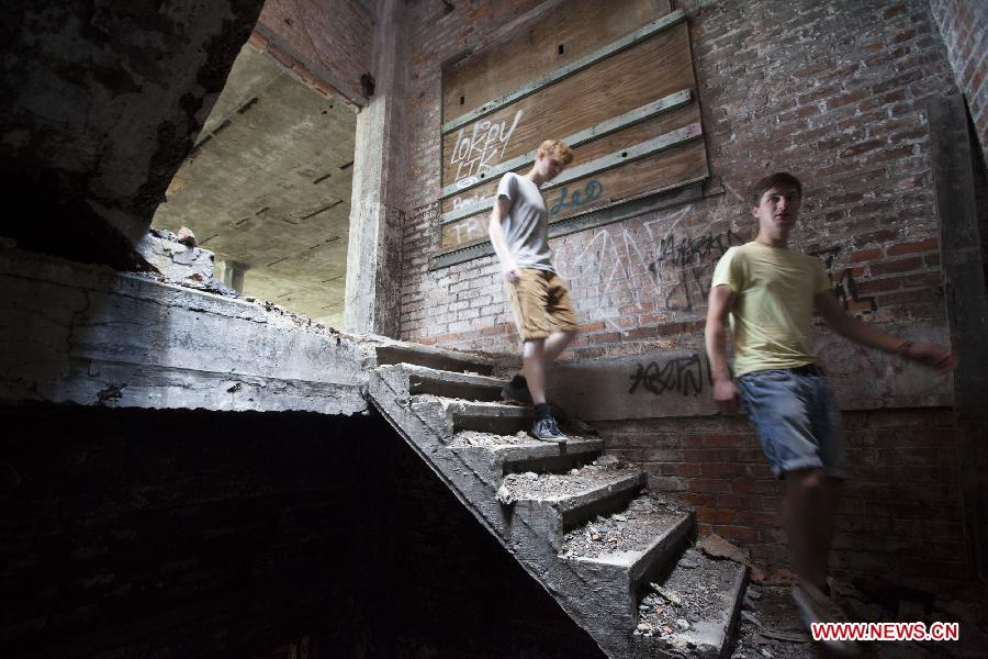 Two Belgian tourists explore the Packard Plant, an abandoned auto factory, in Detroit, midwest city of the United States, July 19, 2013. U.S. city Detroit filed for bankruptcy Thursday, making it the largest-ever municipal bankruptcy in U.S. history, local media reported. (Xinhua/Marcus DiPaola)