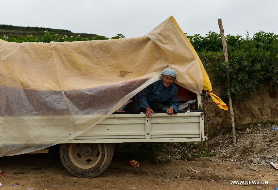 A villager rests on a truck at quick-hit Yongguang Village of Minxian County, northwest China's Gansu Province, July 23, 2013. The death toll has climbed to 94 in the 6.6-magnitude earthquake which jolted a juncture region of Minxian County and Zhangxian County in Dingxi City Monday morning. (Xinhua/Liu Xiao)