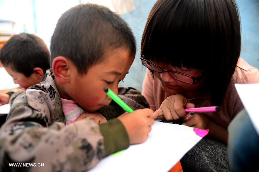 "A volunteer teaches children in a ""Tent School"" in quake-stricken Yongxing Village of Minxian County, northwest China's Gansu Province, July 24, 2013. 10 university student volunteers teach various courses for those in need in the ""Tent School"" in quake-stricken Yongxing Village on Wednesday. (Xinhua/Zhang Meng)"