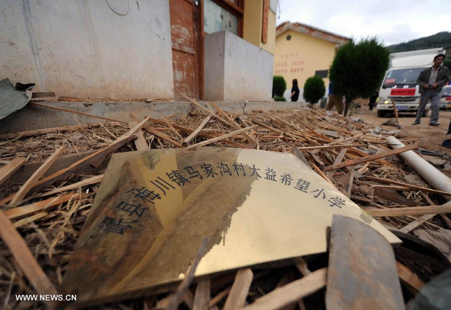 A doorplate bearing the school name lies on ruins at a primary school in the quake-hit Majiagou Village in Meichuan Township, Minxian County, northwest China's Gansu Province, July 24, 2013. Over 360 schools in Gansu's Minxian and Zhangxian counties were destroyed by the 6.6-magnitude quake that occurred on Monday, affecting 77,000 students, according to the local authorities. (Xinhua/Luo Xiaoguang)