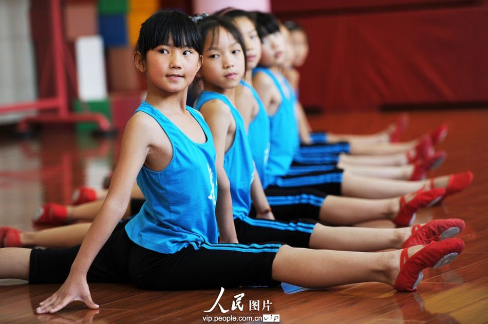Children of migrant workers do the splits and practice dancing in the Youth Palace of Yuyao City, east China's Zhejiang province. (Photo by Chen Binrong/ vip.people.com.cn)