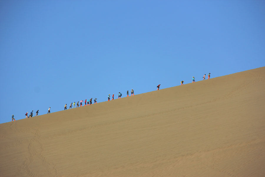 A line of people climb up one of Mingsha Mountain's dunes. (CRIENGLISH.com/William Wang)