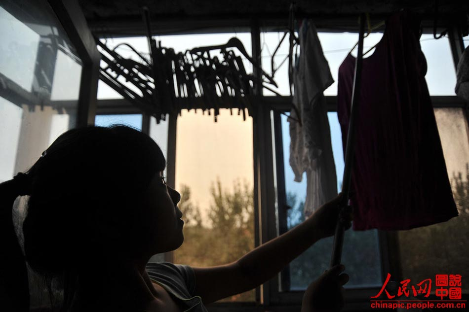 Gao hangs up the washed clothes at home in Tianjing on July 12, 2013. She has learned to take care of the whole family since she was five.
