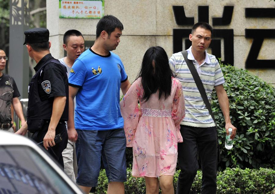 A suspect is arrested in the Chenghua District of Chengdu, capital of southwest China's Sichuan Province, July 31, 2013. A gun fight took place as drug dealers resisted arrest from the police. One suspect jumped from a building and was killed while another two were arrested. (Xinhua/Xue Yubin)
