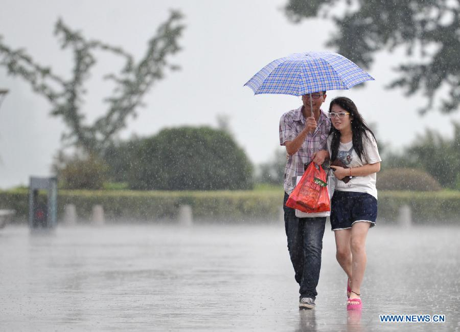 Citizens walk in the rain in Nanjing, capital of east China's Jiangsu Province, July 31, 2013. An artificial precipitation brought coolness to citizens in Nanjing. (Xinhua/Lang Congliu)