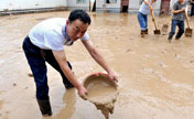 People clean silt after heavy rainfall in NW China