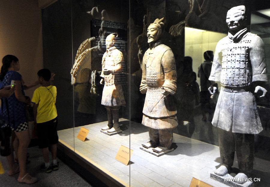 Tourists visit the terracotta warriors and horses at the Emperor Qinshihuang's Mausoleum Site Museum in Xi'an, capital of Northwest China's Shaanxi province, Aug 20, 2013. The museum witnessed a tourism peak since August.[Photo/Xinhua]