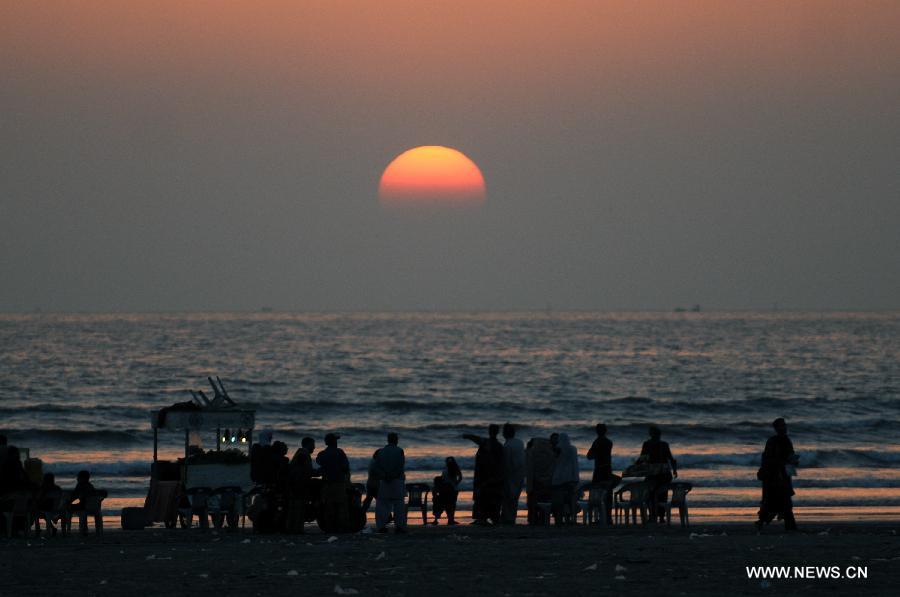Tourists enjoy sunset at Clifton beach in Karachi - People's